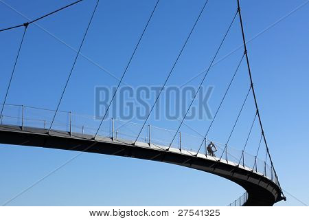 cyclist crossing a curve-shaped suspended bridge, blue sky