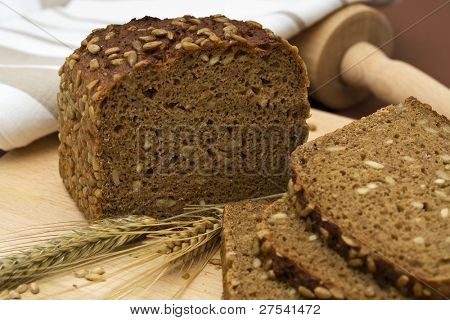 whole grain bread and slices with wheat and barley, rolling pin, towel