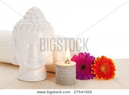 Buddha head, rolled towel, burning aromatic candle and flowers on straw mat, white background