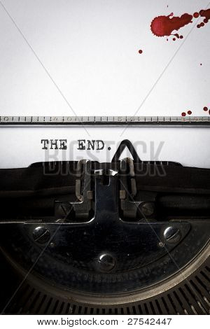"Words ""The End"" written on old typewriter, closeup, blood stains on paper"