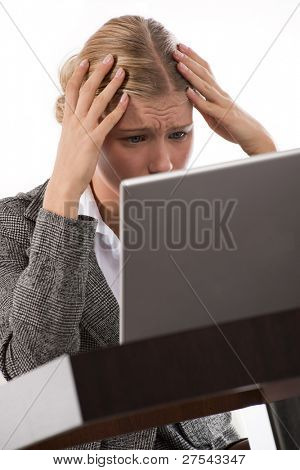 Young businesswoman receiving bad financial news while working on her laptop