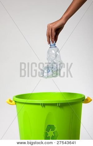 Woman's hand putting a plastic bottle into a recycling bin