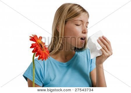 Young woman blowing her nose. Flowers representing seasonal allergens.