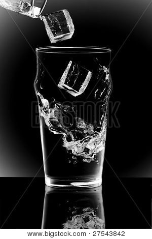 Ice splashing into a glass of water, see also blue tone image
