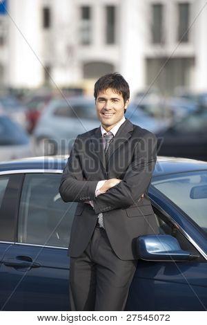 Junger Geschäftsmann stützte sich auf sein Auto