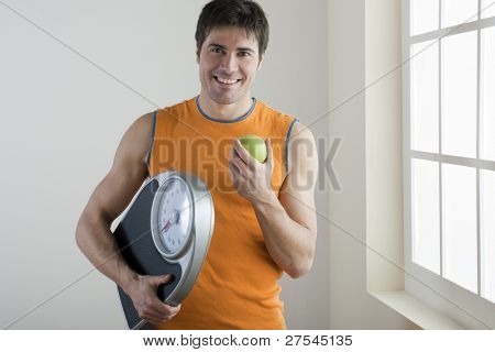 Sportsman holding scale and apple; concept: healthy lifestyle