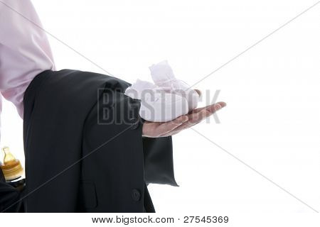 Man hand holding baby shoe and business jacket, milk bottle on his trousers pocket. Concept: modern man, multi-tasking