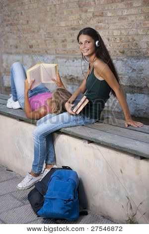 Teenage girls studying on a bench