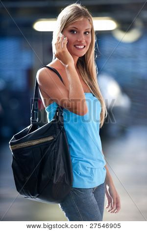 Young woman speaking on the phone while at an underground car park