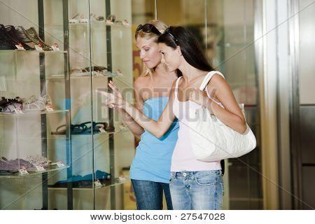 Jovens mulheres olhando pela janela da loja
