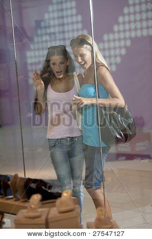 Young women looking through shop window