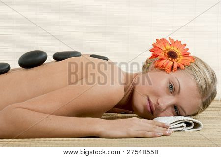 Attractive young woman with warm massage stones lined up on her back.