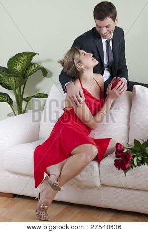 Woman receiving red roses and a heart shaped gift on Valentine's Day, Wedding Anniversary or Birthday