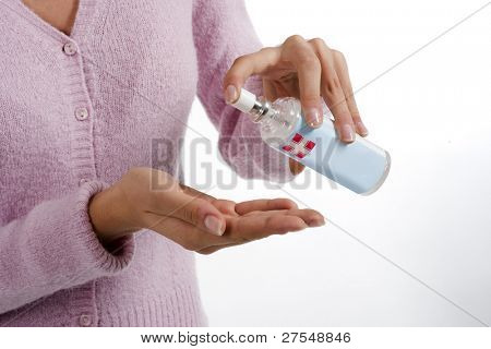 Woman squirts a squirt of antibacterial liquid soap into her palm.