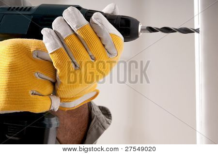 Man drilling a hole in the wall