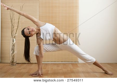 Young woman doing yoga at home/gym