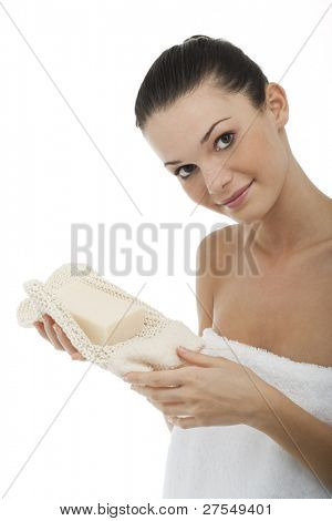 Young woman wrapped in towel holding soap