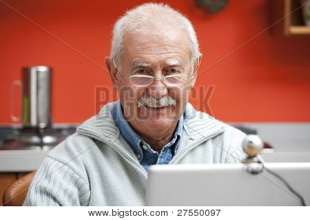 Senior man speaking through webcam in his kitchen