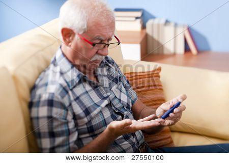 Senior hombre haciendo prueba de azúcar en la sangre en el país