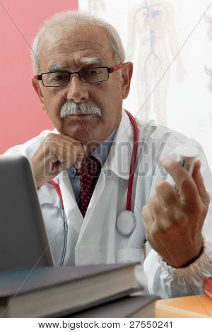 Senior doctor speaking with patient through webcam