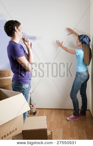Young couple discussing about where to place paintings or pictures