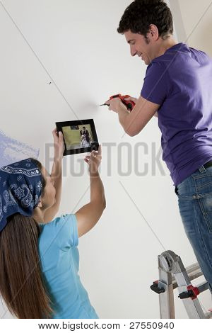 Just married couple hanging their wedding picture in their new home