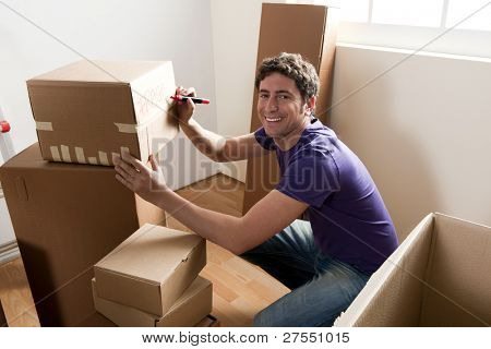 Young man packing boxes