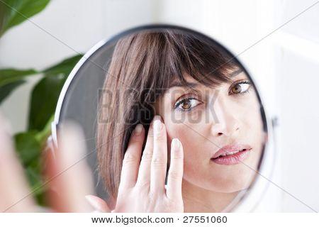 Mujer mirando a sí misma en el espejo