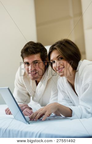 Relaxed couple working in bed