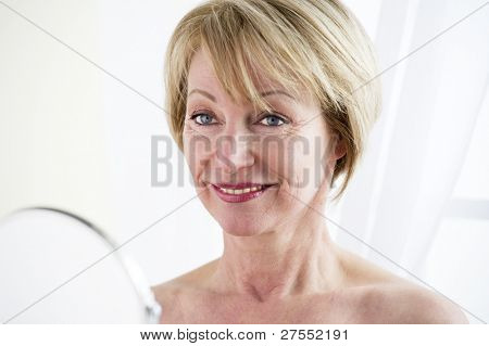 Beautiful mature woman making up