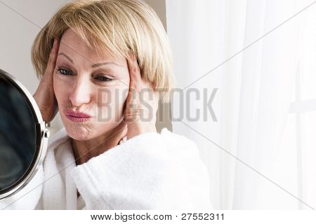 Mature woman looking at herself in the mirror