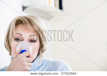 Woman Using A Nebulizer for respiratory treatment