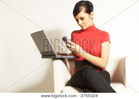 Attractive brunette businesswoman sitting with Laptop and phone on the white chair