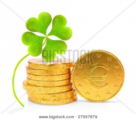 Golden euro coins with four leaf clover on a white background.