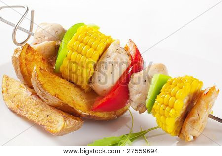 Skewer with corn and meat, American potatoes