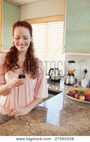 Smiling woman writing text message in the kitchen