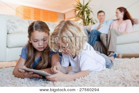 Siblings using tablet together on the living room floor