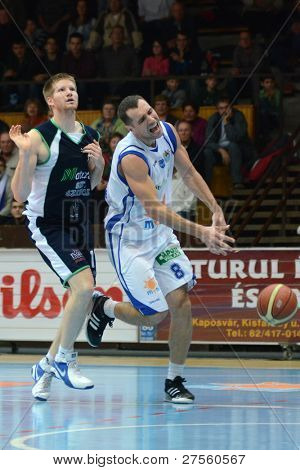 KAPOSVAR, HUNGARY - DECEMBER 10: Balazs Szoke (in white) in action at a Hungarian Championship basketball game Kaposvar (white) vs. Szeged (blue) on December 10, 2011 in Kaposvar, Hungary.