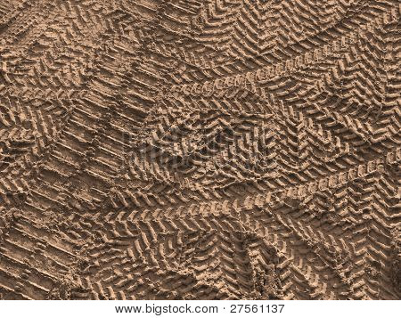 warm toned crisscross tire tracks on construction site as a background