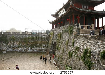 SUZHOU, CHINA - NOVEMBER 23: Tourists visit the Panmen Gate Tower, a part of the ancient city wall built in 514 BC on November 23, 2011 in Suzhou, China. The city wall surrounds and protects the city.