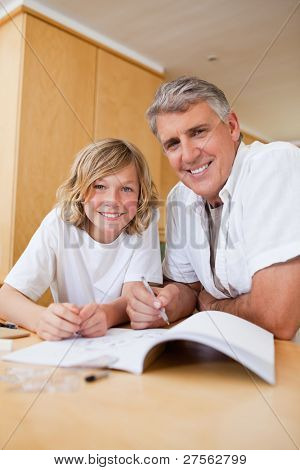 Boy getting help with his homework from father