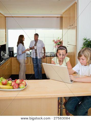 Geschwister mit ihrem Notebook in der Küche und Eltern dahinter