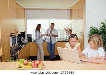 Kinder mit ihrem Laptop in der Küche und Eltern dahinter