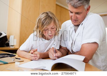 Boy gets help help with homework from father