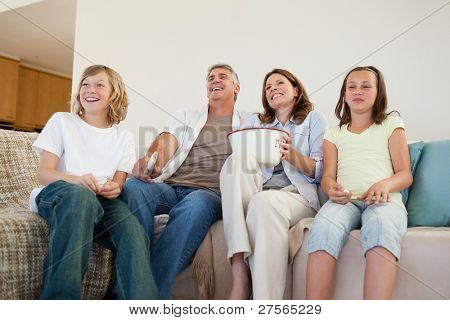 Family on the couch watching tv together