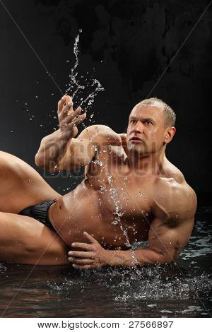 Undressed tanned bodybuilder in rain lies on the wet floor and dabbles.