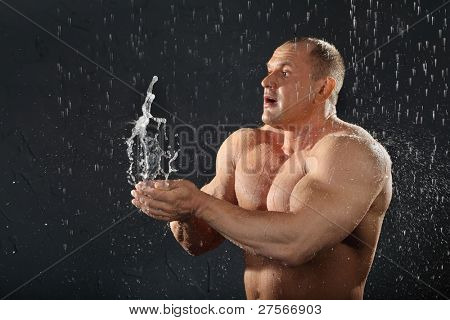 Undressed tanned bodybuilder in rain throws water in his hands