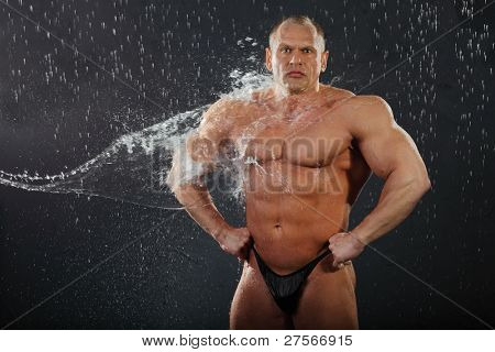 Water flows on undressed tanned bodybuilder in rain.