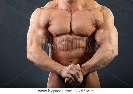 Músculos fortes do tronco e mão de despido bronzeada fisiculturista molhado