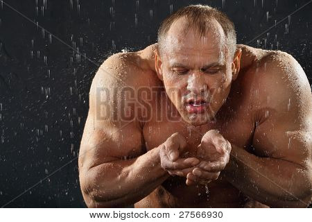 Undressed tanned bodybuilder in rain drinks water from hands.